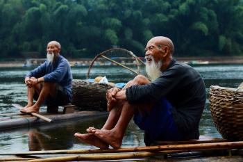 Two Men Sitting on Riverbank