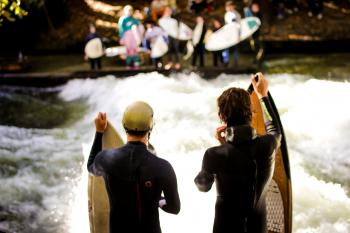 Two Men Wearing Black Wet Suits Holding Brown Wooden Surfboards