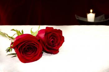 Two red roses and a candle on the background