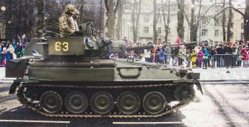 Two Soldiers Ride on Green Military Tank Surrounded With People