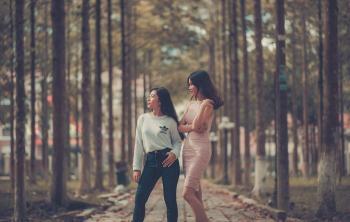 Two Woman Standing on Sidewalk Near Trees