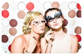 Two Woman Taking Photo in Photobooth Holding Black and Pink Masquerade Mask