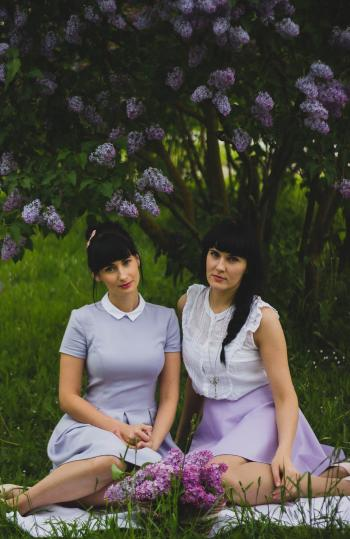Two Women Wearing Purple Dress Sitting Side-by-side on Grass Field