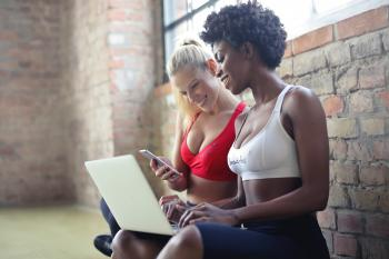 Two Women Wearing Red and White Sports Bras Sitting Near Brown Wall Bricks