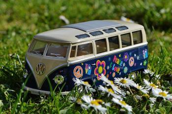 Volkswagen Beige and Blue Van Scale Model Near White Daisy Flower during Daytime