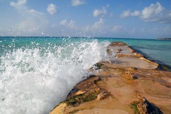 Water breaking over a seaside barrier