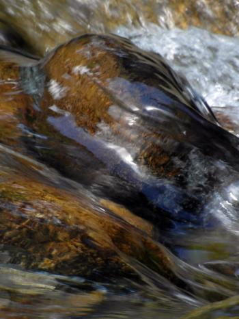 Water over smooth boulders in river