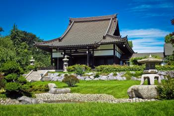 White and Black Temple Surrounded by Green Grass Field during Daytime