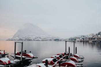 White and Red Boats on Dock Near White Snowy Mountain
