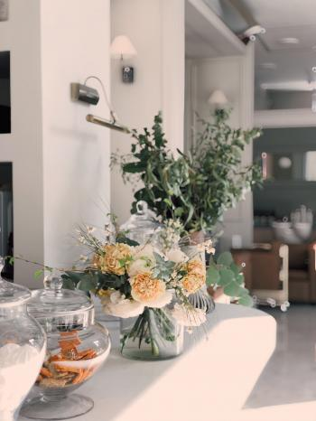 White and Yellow Petaled Flowers Centerpiece Near Clear Glass Jars on Top of White Wooden Table