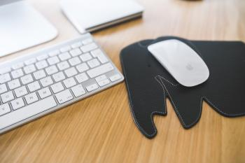 White Apple mouse and keyboard on the black Elephant Pad