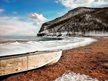 White Boat on Seashore Near Mountain Under White and Blue Sky