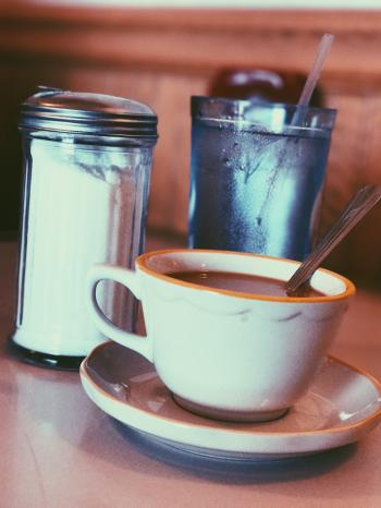 White Ceramic Mug Fill With Coffee Beside Condiment Shaker