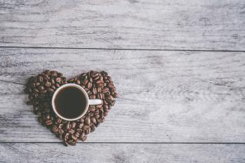 White Ceramic Mug Filled With Brown Liquid on Heart-shaped Coffee Beans