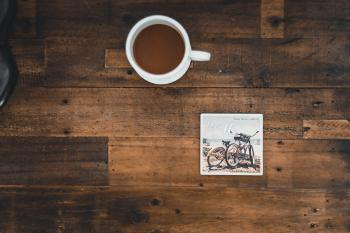 White Ceramic Mug With Coffee Beside Photo of Two Mountain Bikes