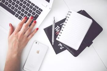 White laptop, female hand, note, pen, phone, desk