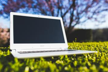White laptop on a green meadow