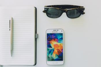 White Samsung Smartphone Beside Sunglasses,pen and White Notebook