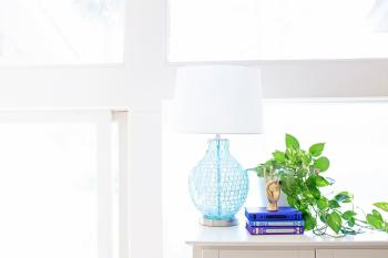 White Table Lamp on Sideboard Near Plant and Books