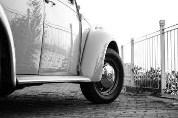 White Volkswagen Beetle Near White Metal Fence