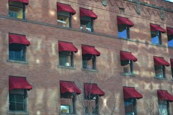 Windows with burgundy canopies along the brick wall of the building
