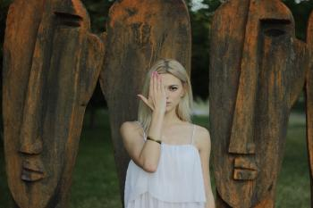 Woman Covering Face With Right Hand in Front of Large Tribal Head Statue