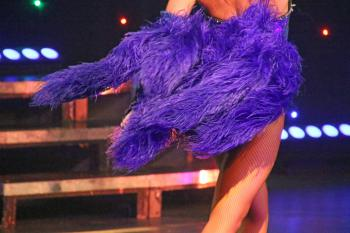 Woman dancer wearing purple feather dress