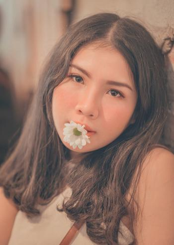 Woman Having a White Daisy on Her Mouth