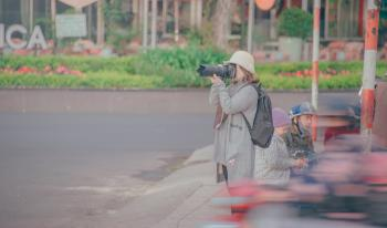 Woman Holding Black Dslr Camera Taking Picture