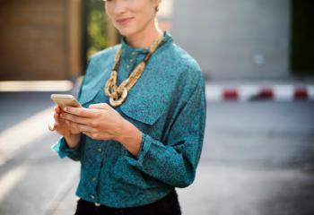 Woman Holding Iphone Wearing Long-sleeved Shirt And Gold Necklace