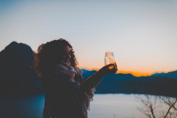 Woman Holding Mason Jar With String Light With Lake and Mountain over View during Golden Hour