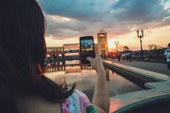 Woman Holding Smartphone Capturing Sunset