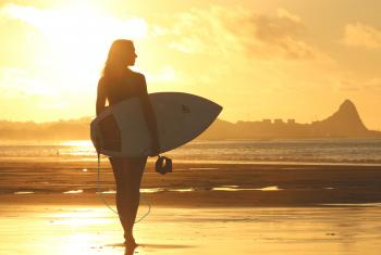 Woman Holding Surf Board Standing on Shoreline during Sunset