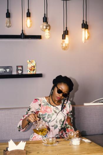 Woman Holding Teapot Near Table