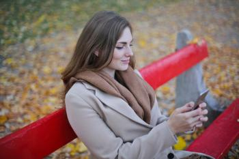 Woman in Beige Coat Holding Smartphone Sitting on Bench