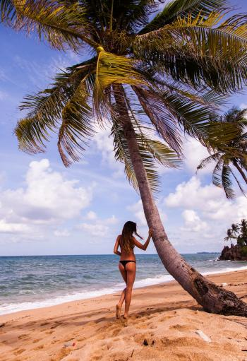 Woman in Bikini Standing Near Tree on Beach Under Cloudy Skies
