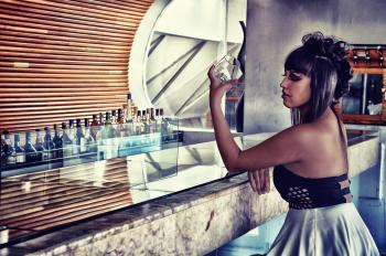 Woman in Black and Gray Backless Dress Sitting in Bar Desk