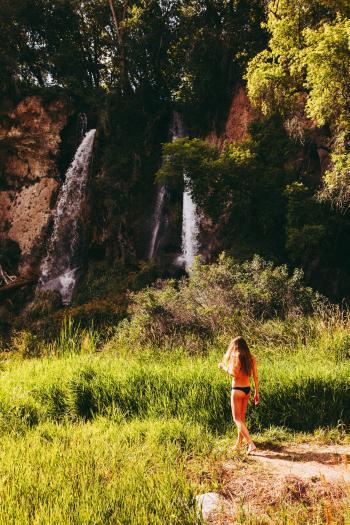 Woman In Black Bikini Bottom Walking Towards Waterfall