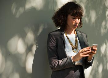 Woman In Black Blazer Holding A Smartphone While Standing Near Wall