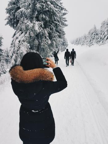 Woman in Black Coat Taking a Picture of Three Person in Front of Her While Walking Through Snow Field