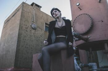 Woman in Black Crop Top Sitting on Brown Chair