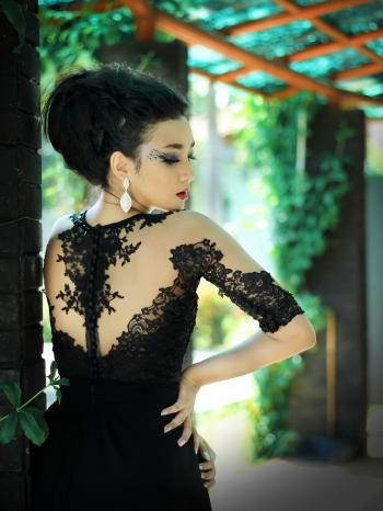 Woman in Black Dress Near Green Vines