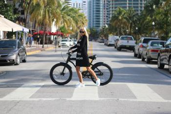 Woman In Black Long Sleeve Shirt Holding Bicycle