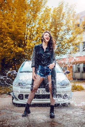 Woman in Black Long-sleeved Top and Blue Denim Shorts Standing in Front of Car