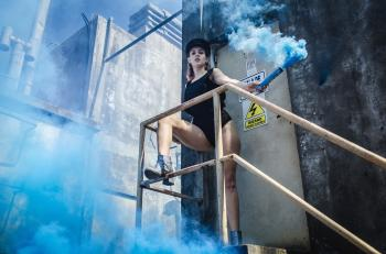 Woman in Black Onepiece Holding Smoke Bomb Near Close Door