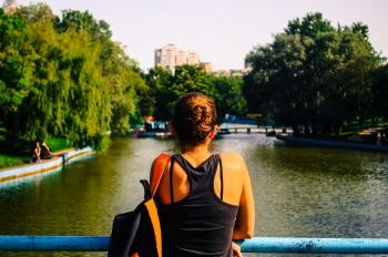 Woman in Black Racerback Top Facing Body of Water and Trees