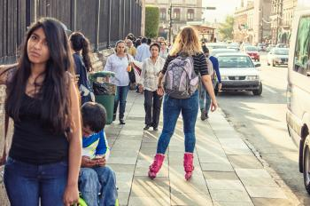 Woman in Black T-shirt, Blue Washed Denim Jeans and Pair of Pink Inline Skates Skating in Street