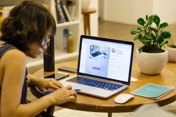 Woman in Black Tank Shirt Facing a Black Laptop Computer on Brown Wooden Round Table