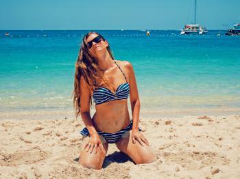 Woman In Blue And White Bikini Kneeling On Sand