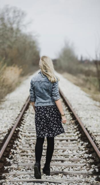 Woman in Blue Denim Jacket, Black Leggings and Black and White Dress Walking on Train Rail